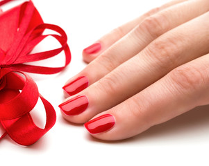 Woman hands with manicure red nails closeup and ribbon