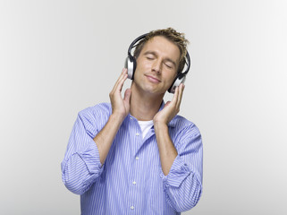Junger Mann mit geschlossenen Augen Musik hören