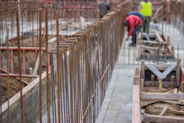 Blurred workers and steel reinforcement in foundation of  new bu