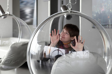 Happy woman posing in glass chair
