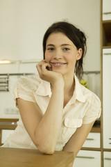 Junge Frau lehnt an der Küchenarbeitsplatte,lächelnd,close-up,Portrait