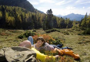Ehepaar liegt in der Wiese mit Bergen im Hintergrund