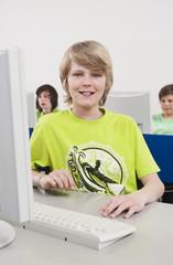 Deutschland,Emmering,Teenager (14-15) lächelnd mit Studenten,die mit Computer im Hintergrund