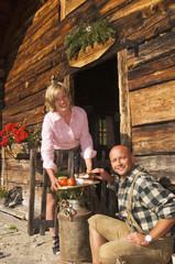 Frau serviert Snack vor der Hütte