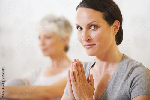 canvas print picture Zwei Frauen,Frau im Vordergrund mit gefalteten Händen
