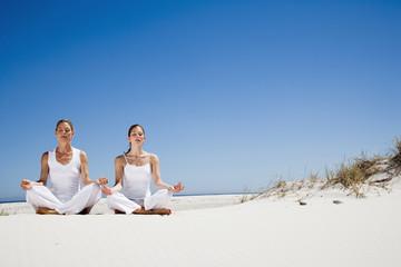 Zwei Frauen,die Ausübung von Yoga am Strand