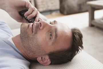 Deutschland,Mann liegt auf der Couch mit Handy
