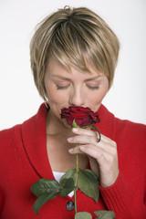 Frau riecht an einer Rose