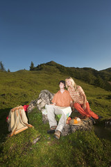 Junges Paar sitzt auf Felsen , die Ansicht betrachten .