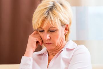 Seniorin fasst sich mit Kopfschmerzen an Stirn