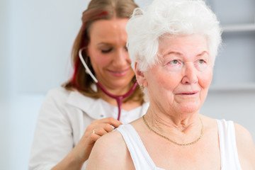 Doktor bei Atmung abhören von Seniorin in Arztpraxis