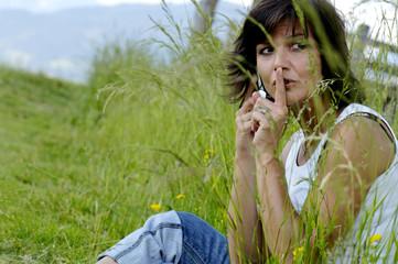 Frau sitzt im Feld mit Handy,Finger auf die Lippen