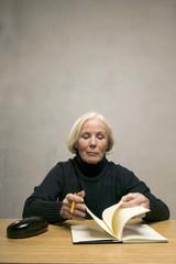Ältere Frau sitzt am Tisch mit Buch und Bleistift