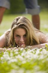 Junge Frau liegt in der Wiese mit jungen Mann im Hintergrund