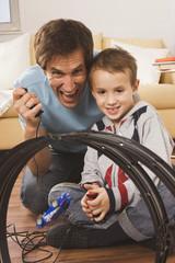 Vater und Sohn ( 4-5) spielt mit Spielzeug- Rennbahn