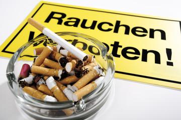 Volle Aschenbecher vor Rauchverbot Schild