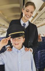Deutschland,München,Bayern,Junge mit Hut Kapitäne salutierte vor der Stewardess in der Economy- Klasse-Verkehrsflugzeug