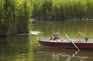 Italien,Südtirol,Junges Paar in Ruderboot liegen