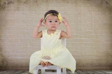 Kind im gelben Kleid vor Alter Mauer