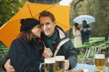 Deutschland,Bayern,Englischer Garten,Paar sitzt im regnerischen Bier Garten,hält Dach,Portrait