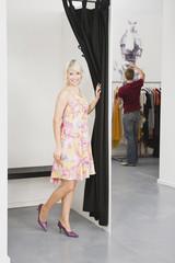 Junge Frau in der Umkleidekabine,Mann im Hintergrund