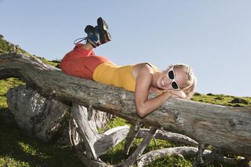 Junge Frau liegt auf der Vorderseite auf gefallenen Baumstamm , lächelnd.