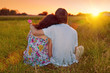Young couple sitting back to camera on grass, looking at sunset