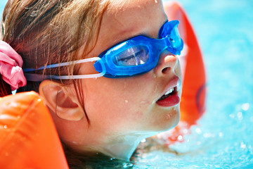 Kids with goggles in swimming pool.