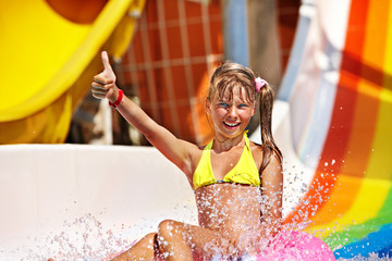 Child in bikini sliding water park.
