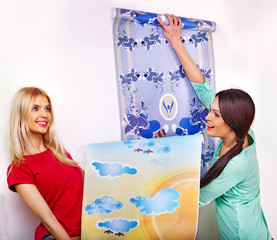 Women glues wallpaper at home.