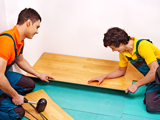 Men laying parquet at home