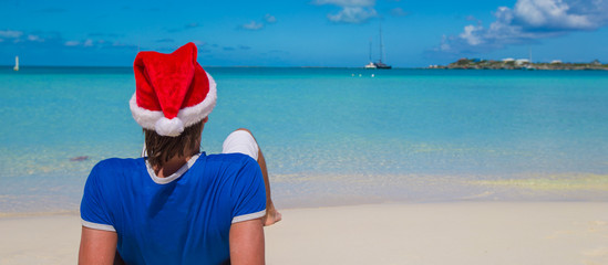 Back view of young man in santa hat on tropical caribbean beach