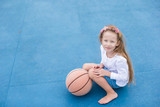 Little girl with basketball on the outdoor court at tropical poster