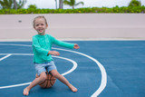 Little girl have fun with basketball on the outdoor court poster