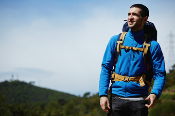 Hiker standing on the mountain hill and looks into the distance