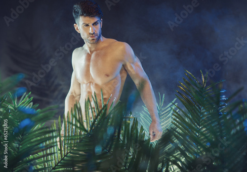 Tall and muscular man in the rain forest
