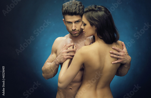 Nude couple touching their fit bodies