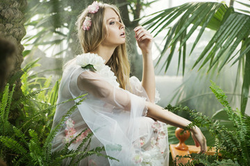 Sensual young lady among the greenery