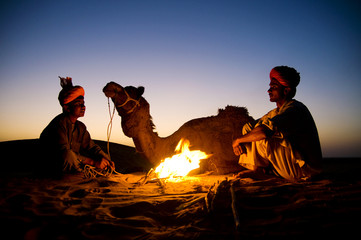 Indigenous Indian Men Resting By The Bonfire With Their Camel