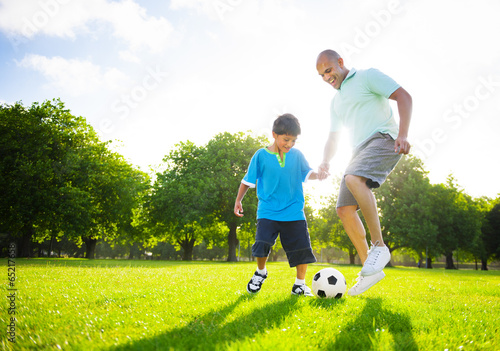 canvas print picture Little Boy Playing Soccer With His Father