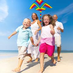 Family running with kite on beach