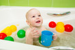 happy kid boy taking bath and playing with toys