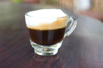 Hot  espresso with milk and foam in cup.