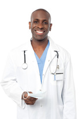 Friendly middle aged male doctor posing