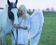 Blond angel looking after the horse