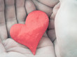 Red cloth heart in hands. Selective focus. Color toned image.