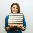 Красивая радостная девушка с тяжелыми книгами в руках