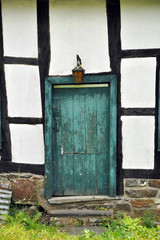 Timber frame facade with a closed crooked old green wooden door