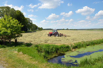 A farm tractor pulling a hay rake in a field to clew the grass
