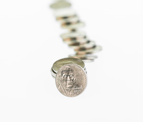 Fallen stack of nickels over white background
